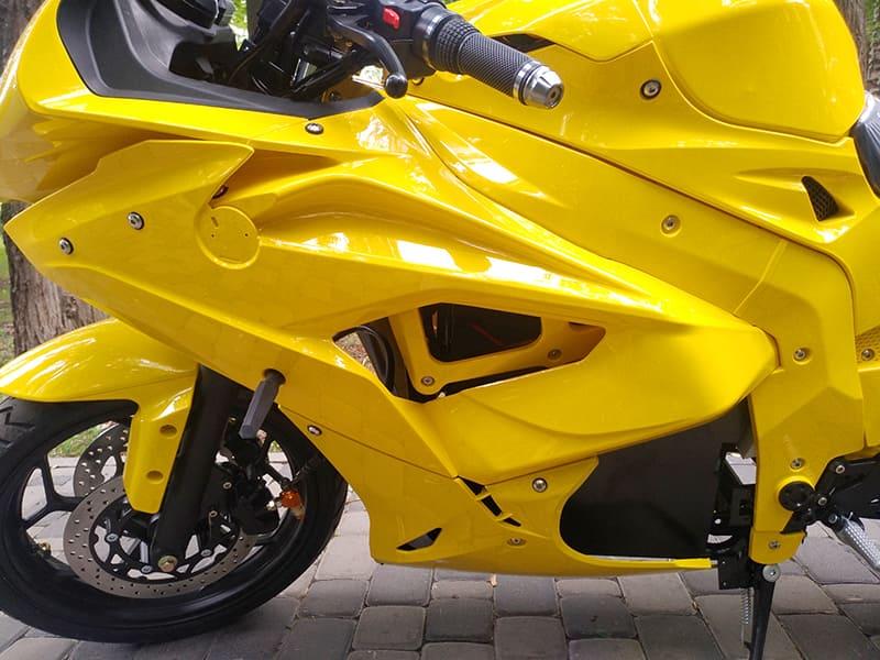 Левая передняя сторона кузова желтого электромотоцикла Electrowin EM-BM
