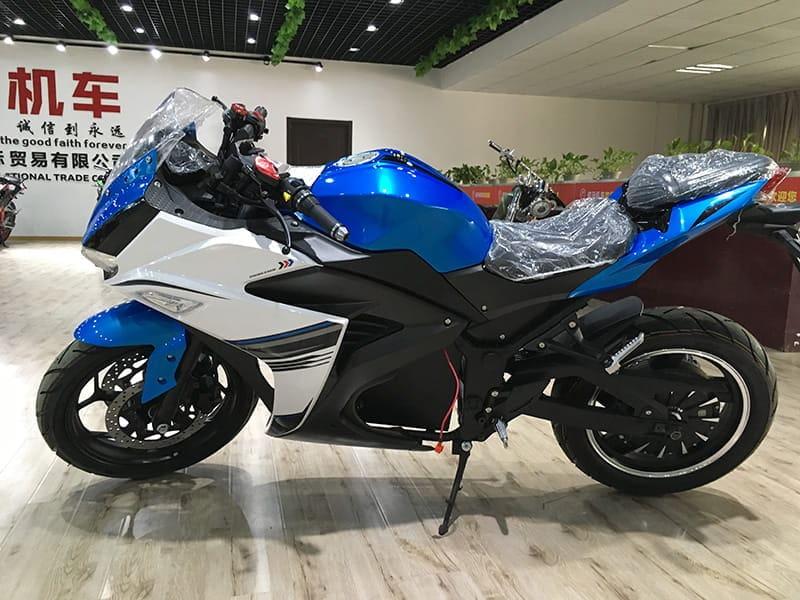 Электрический мотоцикл Electrowin EM-120 бело-синий в павильоне. Вид слева