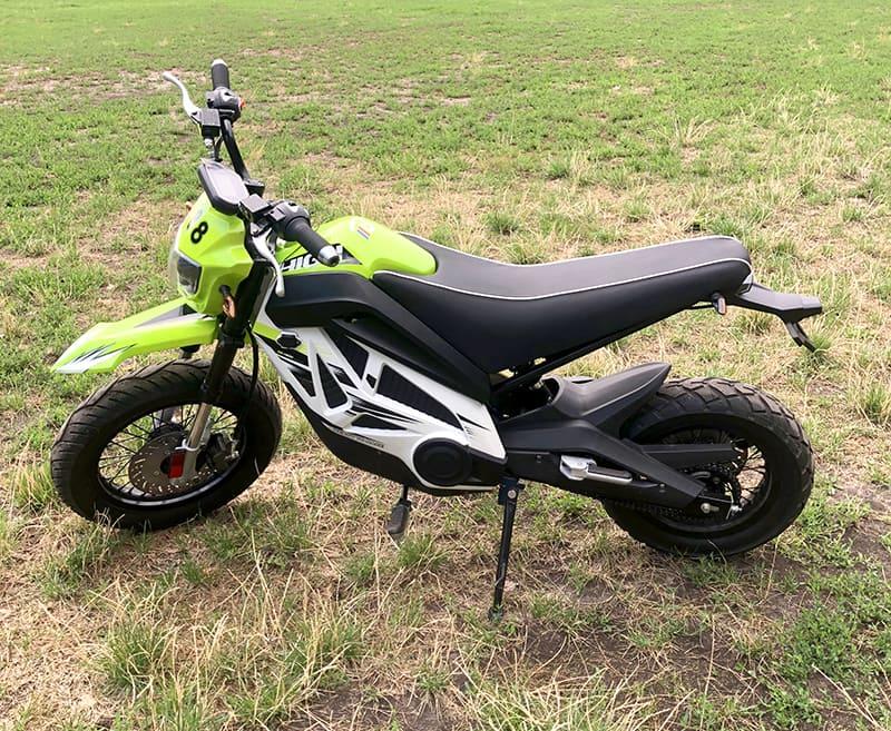 Светло-зеленый кроссовый электромотоцикл Electrowin EMB-188 на травке, вид слева