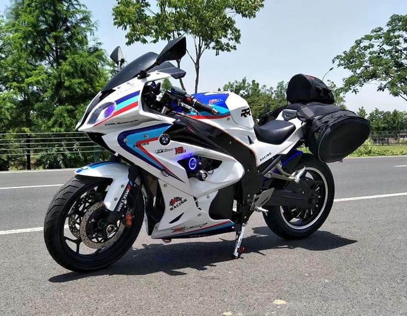 Электромотоцикл Electrowin EM-BM, белый с навесными задними багажниками на шоссе. Вид слева