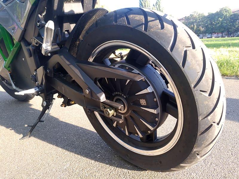 Заднее колесо серебристо-зеленого электрического мотоцикла Electrowin EM-130, вид сзади слева
