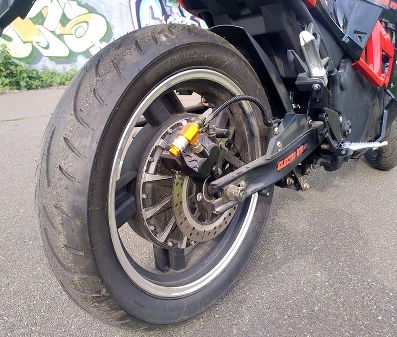 Заднее колесо красно-черного электромотоцикла Electrowin EM-130 с электродвигателем, вид справа