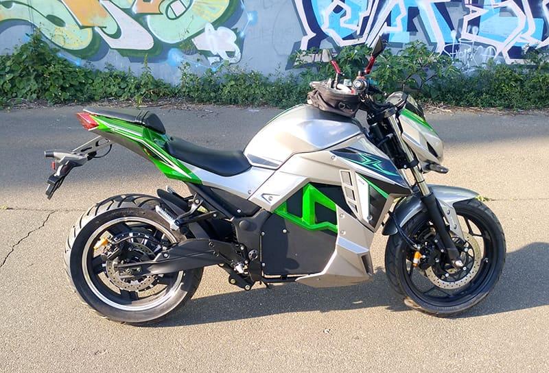 Серебристо-зеленый злектромотоцикл Electrowin EM-130 на улице летним днем