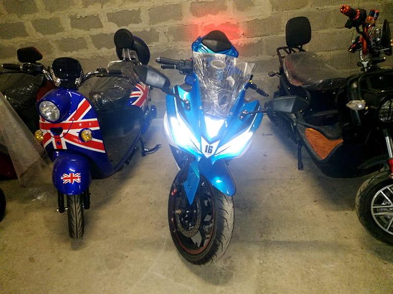 Электромотоцикл Electrowin EM-120 бело-синий с включенными фарами. Вид спереди
