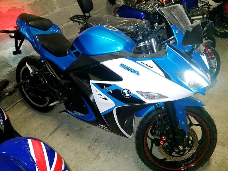 Электромотоцикл Electrowin EM-120 бело-синий с включенными фарами. Боковой вид