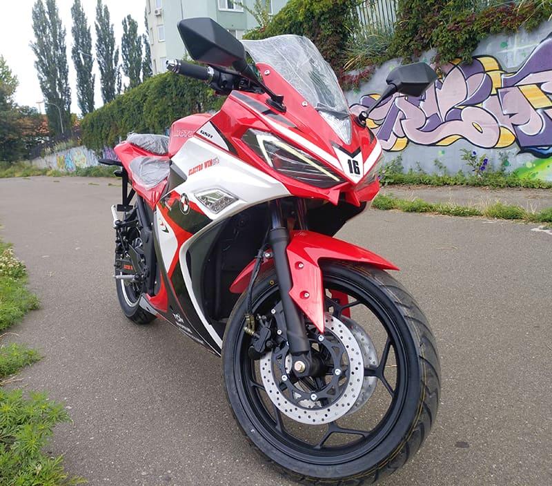 Красный электрический мотоцикл Electrowin EM-120. Вид спереди с повернутым рулем