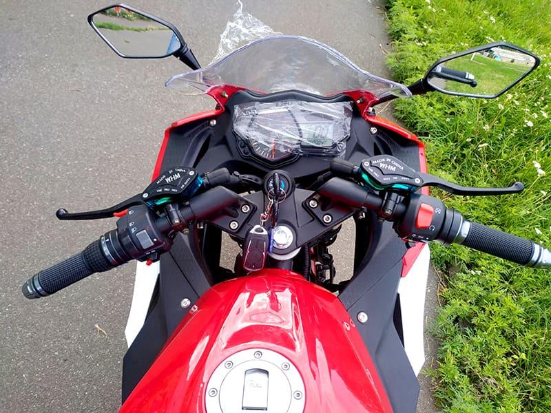 Руль, панель управления и ключ в замке включения красного электромотоцикла Electrowin EM-120. Вид с водительского места