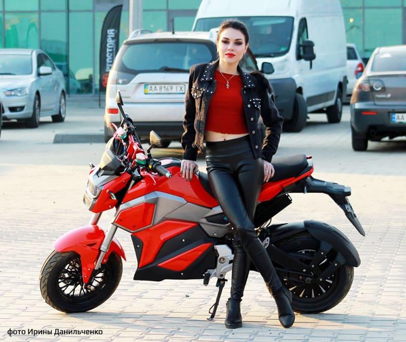 Электромотоцикл Electrowin EM-125 в городе с фотомоделью во весь рост. Вид сбоку