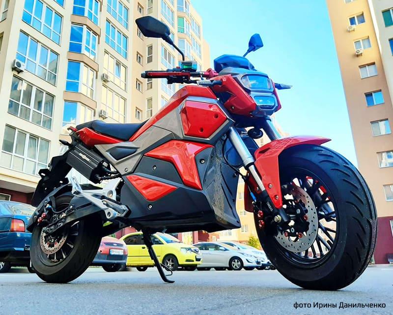 Электромотоцикл Electrowin EM-125, красный, в городе. Правый полупрофиль