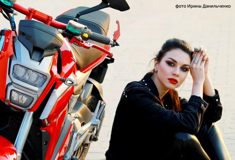 Фотомодель рядом с красным электромотоциклом Electrowin EM-125. Фары крупным планом
