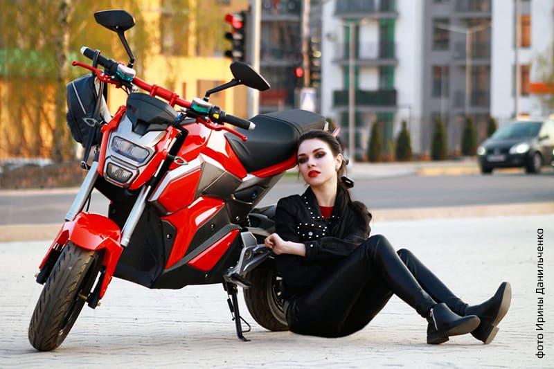 Красный электромотоцикл Electrowin EM-125 в городе с фотомоделью, сидящей рядом. Вид спереди слева