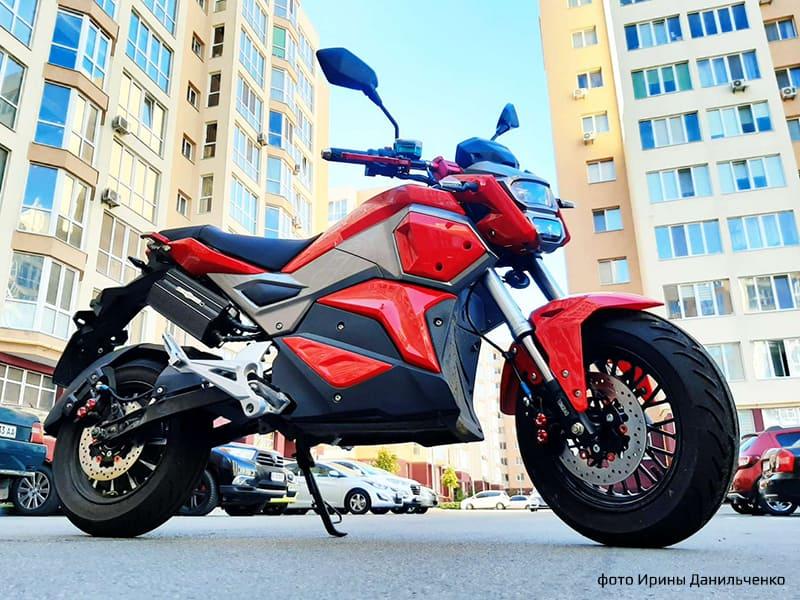 Красный электромотоцикл Electrowin EM-125 в городском ландшафте. Фото снизу справа