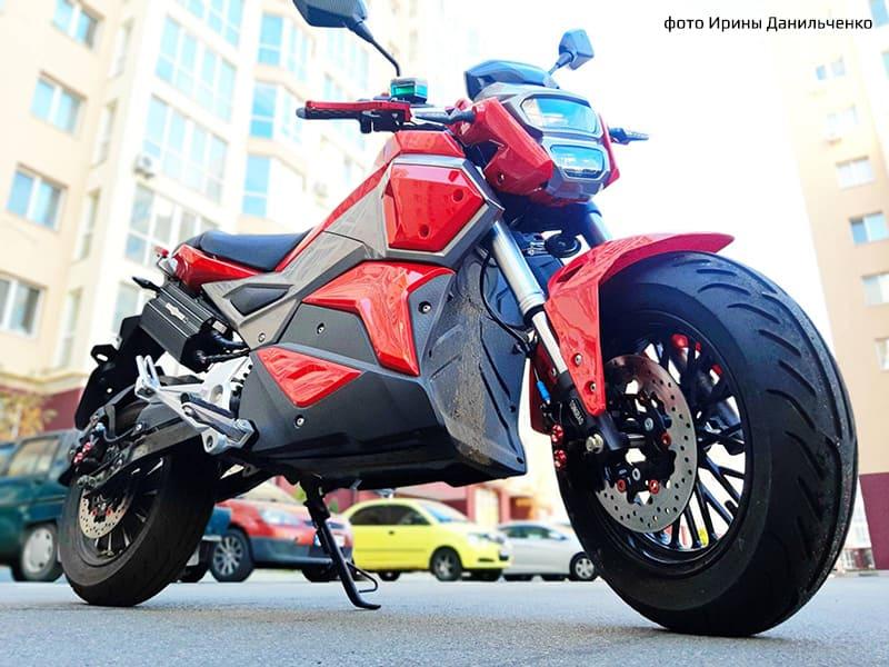 Электромотоцикл Electrowin EM-125 красного цвета на фоне города. Фото спереди снизу справа