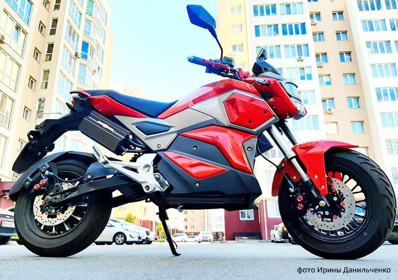 Electrowin EM-125 красного цвета на фоне города. Правый профиль
