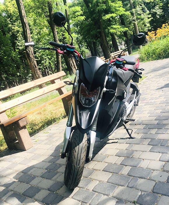 Черный электромотоцикл Electrowin EM-126 в летнем парке, вид спереди