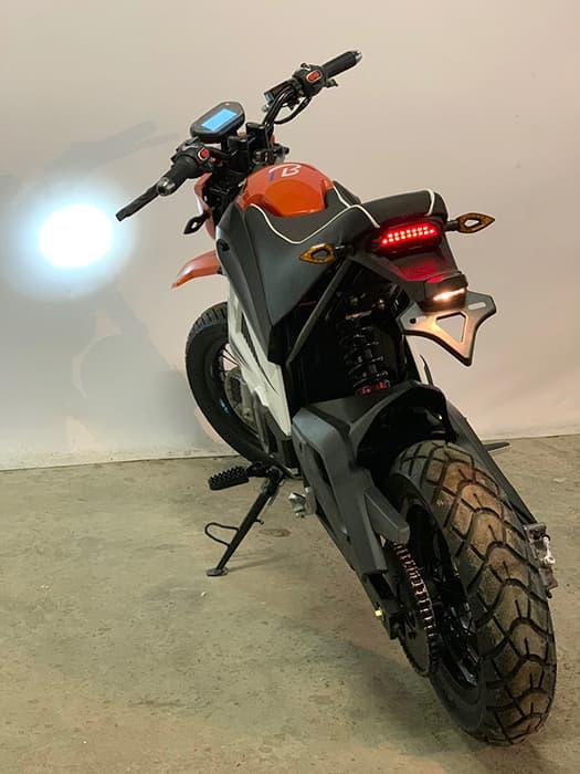 Оранжевый кроссовый электро мотоцикл Electrowin EMB-188 с включенной передней фарой, вид сзади сбоку