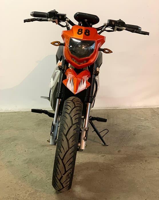 Оранжевый кроссовый электрический мотоцикл Electrowin EMB-188 с включенной передней фарой, вид спереди