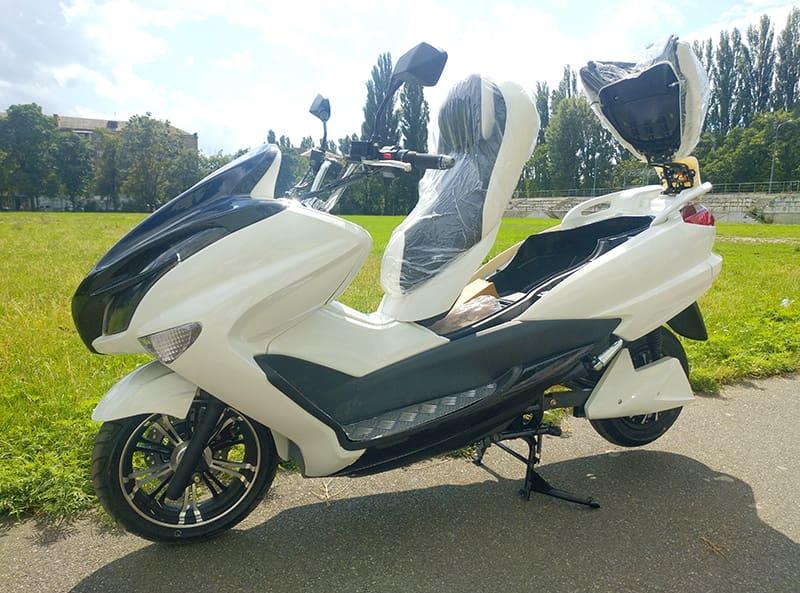 Белый макси скутер Electrowin T-3 Maxi с открытым багажником под передним креслом. Вид слева