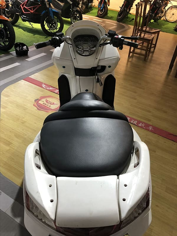 Кресло, руль и панель управления белого электроскутера Electrowin T-3 Maxi. Вид сзади сверху