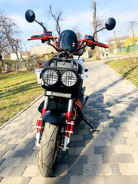Электрический скутер Electrowin ZUMA оранжевого цвета в парке, фронтальный вид